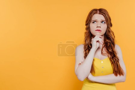 Photo for Beautiful pensive redhead girl propping chin and looking away isolated on yellow with copy space - Royalty Free Image
