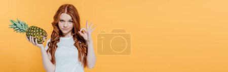 Photo for Panoramic shot of beautiful redhead girl looking at camera and showing ok sign while posing with pineapple isolated on yellow - Royalty Free Image