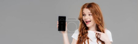Photo for Panoramic shot of beautiful excited redhead girl pointing with finger at smartphone with copy space isolated on grey - Royalty Free Image