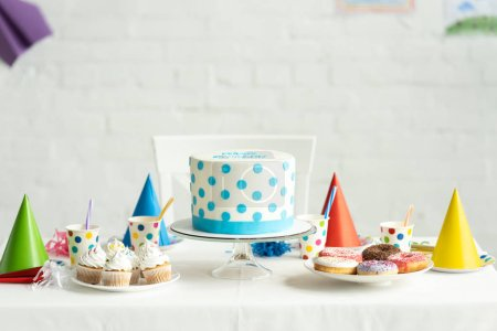 Photo for Delicious birthday cake with cupcakes, doughnuts and paper cups on festive table - Royalty Free Image