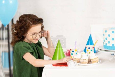 Foto de Niño adorable sentado en la mesa con pastelillos durante la celebración de cumpleaños - Imagen libre de derechos