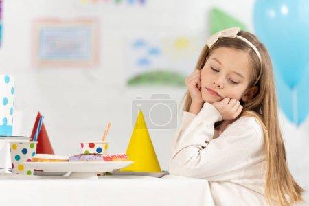Foto de Chico molesto sentado en la mesa con Donuts y gorras de fiesta durante la celebración de cumpleaños - Imagen libre de derechos