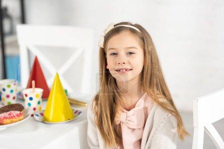Foto de Niño adorable en la mesa de cumpleaños con decoraciones festivas mirando a la cámara durante la fiesta - Imagen libre de derechos