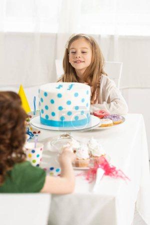 Foto de Niños adorables sentados en la mesa de fiesta con pastel durante la celebración de cumpleaños - Imagen libre de derechos