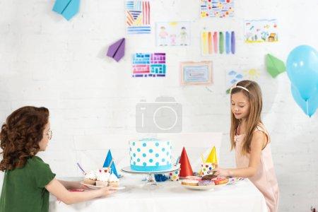 Foto de Niños adorables sentados en la mesa de fiesta con pasteles y pastelillos durante la celebración de cumpleaños - Imagen libre de derechos