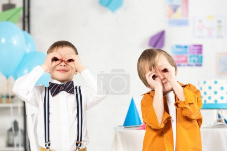 Photo for Adorable preteen boys looking at camera through fingers during birthday party - Royalty Free Image