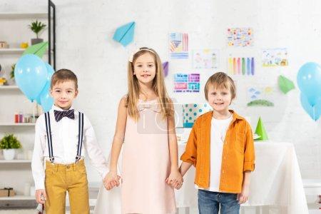 Foto de Niños adorables mirando la cámara y la celebración de las manos durante la fiesta de cumpleaños en casa - Imagen libre de derechos