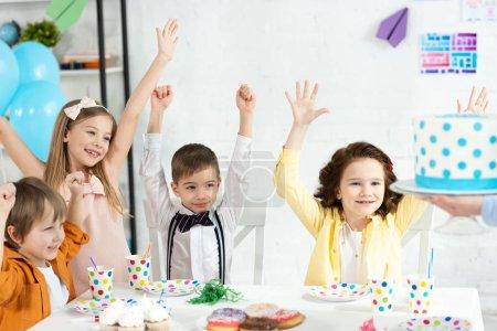 Foto de Niños adorables sentados a la mesa, animando y esperando torta durante la fiesta de cumpleaños - Imagen libre de derechos