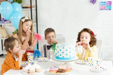 Foto de Los niños sentados en la mesa con pasteles y soplando cuernos de fiesta durante la celebración de cumpleaños - Imagen libre de derechos