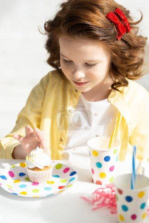 Photo for Adorable preteen looking at cupcake during birthday celebration at home - Royalty Free Image