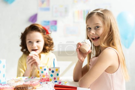 Photo for Adorable kids sitting at party table and eating cupcakes during birthday celebration - Royalty Free Image