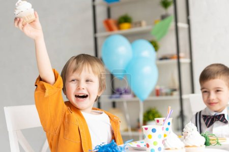 Photo for Selective focus of happy adorable preteen boy holding cupcake during birthday party - Royalty Free Image