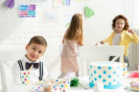 Foto de Enfoque selectivo de niño adorable mirando a la cámara y sentarse en la mesa de fiesta durante la celebración de cumpleaños - Imagen libre de derechos