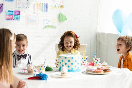 Photo for Adorable smiling kids sitting at table and having fun during birthday party - Royalty Free Image