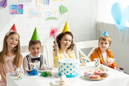 Photo pour Kids in party hats sitting at table and looking at camera during birthday celebration - image libre de droit