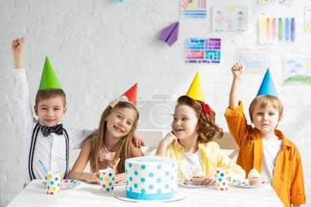 Foto de Niños felices en sombreros de fiesta sentados a la mesa con pastel y celebrando el cumpleaños juntos - Imagen libre de derechos