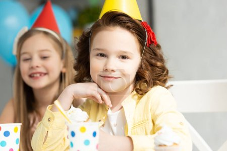 Foto de Niños adorables en gorras de fiesta durante la celebración de cumpleaños - Imagen libre de derechos