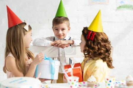 Foto de Niños adorables en gorras de fiesta sentados en la mesa con cajas de regalo durante la fiesta de cumpleaños en casa - Imagen libre de derechos