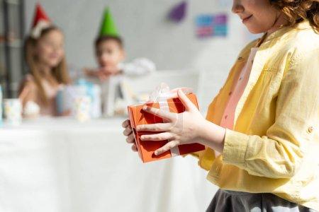 Foto de Vista recortada del niño sosteniendo la caja de regalo durante la fiesta de cumpleaños en casa - Imagen libre de derechos