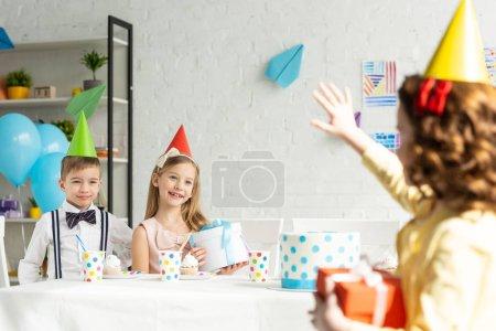 Photo pour Kid agitant à des amis dans des casquettes de partie s'asseyant à la table pendant la célébration d'anniversaire à la maison - image libre de droit