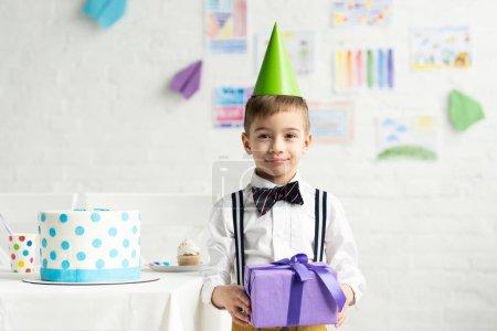Photo pour Garçon adorable dans le chapeau de partie regardant l'appareil-photo et tenant présent pendant la célébration d'anniversaire - image libre de droit