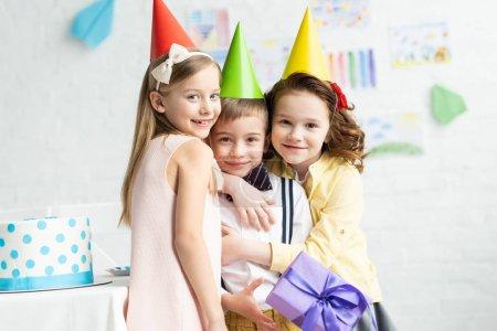 Foto de Niños sonriendo en gorras de fiesta abrazando niño adorable con caja de regalo durante la fiesta de cumpleaños en casa - Imagen libre de derechos