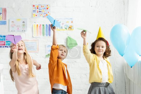 Photo for Adorable kids playing with paper planes during birthday party at home - Royalty Free Image
