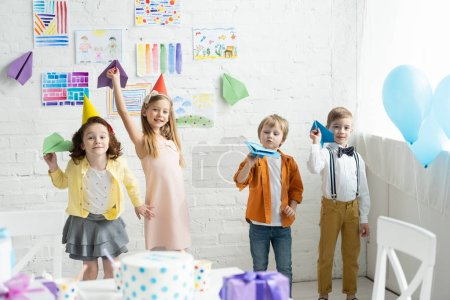 Photo for Adorable smiling kids playing with paper planes during birthday party at home - Royalty Free Image