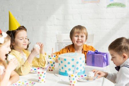 Foto de Niños adorables sentados en la mesa con pastel durante la celebración de fiesta de cumpleaños - Imagen libre de derechos