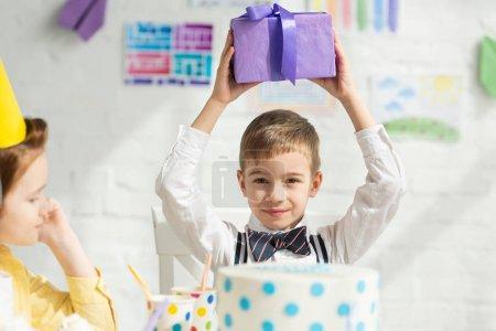 Foto de Enfoque selectivo de niño sosteniendo presente y mirando a la cámara durante la fiesta de cumpleaños - Imagen libre de derechos