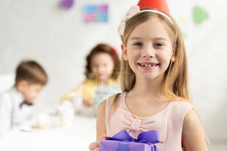 Foto de Adorable niño feliz sosteniendo presente y mirando a la cámara durante la celebración de cumpleaños - Imagen libre de derechos
