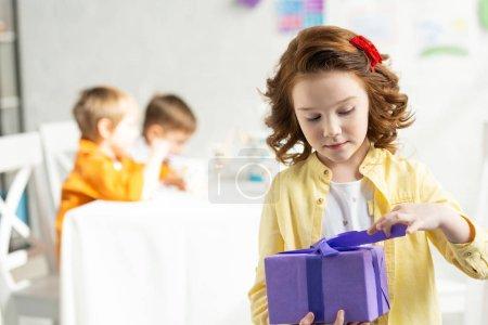 Foto de Enfoque selectivo de la apertura del niño adorable presente durante la celebración del cumpleaños - Imagen libre de derechos