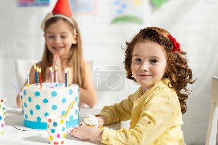 Foto de Niños lindos sentados en la mesa de fiesta durante la celebración de cumpleaños - Imagen libre de derechos