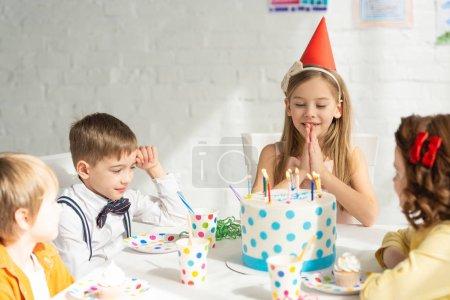 Foto de Niño adorable haciendo por favor gesto y hacer el deseo mientras se sienta a la mesa con los amigos durante la celebración de fiesta de cumpleaños - Imagen libre de derechos