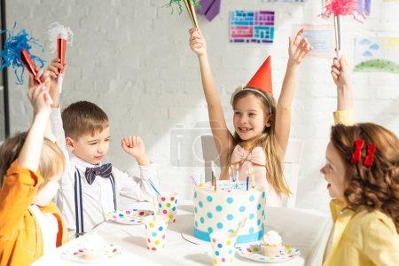 Foto de Niños felices sentados a la mesa con pastel y animando con cuernos de fiesta durante la celebración de cumpleaños - Imagen libre de derechos