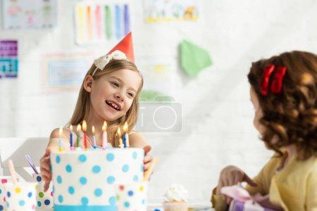 Foto de Niños lindos sentados en la mesa de fiesta con pastel durante la celebración de cumpleaños - Imagen libre de derechos