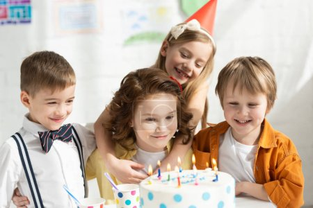 Photo for Adorable kids sitting at party table with cake while celebrating birthday together - Royalty Free Image