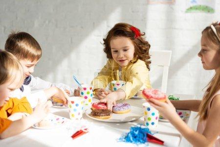 Foto de Niños adorables sentados en la mesa de fiesta mientras celebran el cumpleaños juntos - Imagen libre de derechos