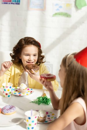 Photo for Adorable kids sitting at party table and eating donuts during birthday celebration - Royalty Free Image