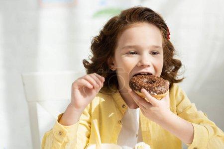 Photo pour Enfant adorable en jaune mangeant délicieux beignet à la table - image libre de droit