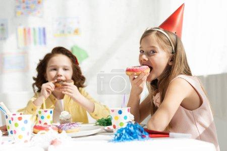 Foto de Niños adorables sentados en la mesa de fiesta y comiendo Donuts durante la celebración de cumpleaños - Imagen libre de derechos