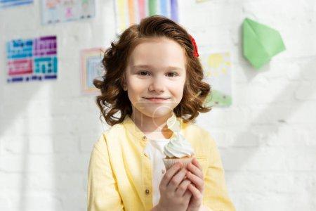 Photo pour Adorable enfant tenant délicieux cupcake et regardant la caméra à la maison - image libre de droit
