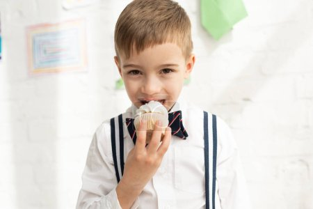 Photo for Adorable preteen boy in bow tie eating cupcake and looking at camera - Royalty Free Image