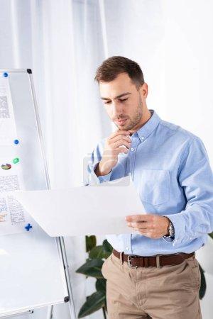 Foto de Hombre de negocios pensativo mirando papel en blanco mientras está de pie cerca de la pizarra en la oficina - Imagen libre de derechos