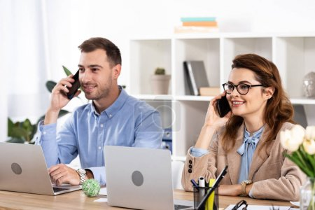 Photo for Cheerful woman sitting near coworker and talking on smartphone in office - Royalty Free Image