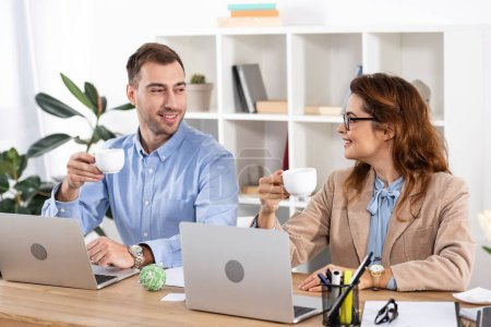 Photo for Cheerful businesswoman in glasses holding cup and looking at coworker in office - Royalty Free Image