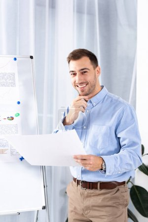 Photo for Cheerful businessman standing near white board and holding blank paper - Royalty Free Image