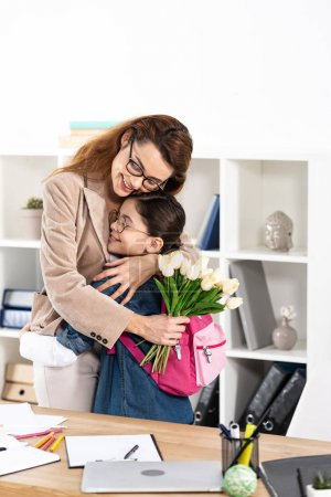 Photo for Happy mother hugging cute daughter and holding flowers in office - Royalty Free Image