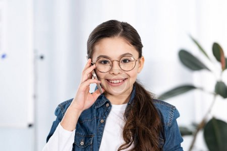 Photo for Cheerful kid looking at camera while talking on smartphone in office - Royalty Free Image