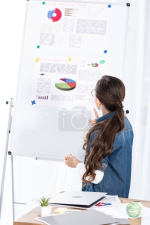 Photo for Back view of kid standing near white board with charts and graphs - Royalty Free Image